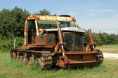 Old rusted tractor in a summer field — Stock Photo