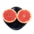 Ripe red grapefruit. The cut fruit on a dark blue plate — Foto de Stock