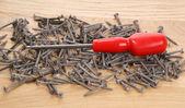 Um monte de parafusos antigos e uma chave de fenda — Foto Stock