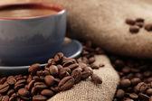 Chicchi di caffè e tazza con il caffè — Foto Stock