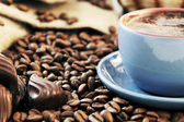 Coffee beans and cup with coffee — Stock Photo
