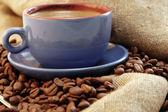 Ziarna kawy i filiżanki z kawą — Zdjęcie stockowe