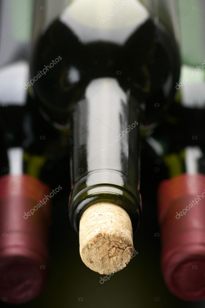 Stack of closed wine bottles lying on dark background. — Photo #4119175