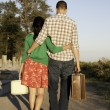 Stock Photo: Couple walking with luggage in hand