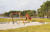Children's playground s on the bank of lake — Stock Photo