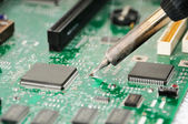 Soldering iron and circuit board — Stock Photo