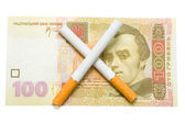 Two cigarettes crossed over one hundred hrivna bill — Stock Photo