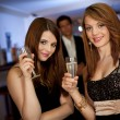Two young women drinking chanpagne - Stock Photo