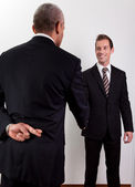 Crossed Fingers At Handshake — Stock Photo