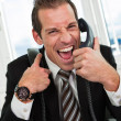 Stressed businessman screaming on the phone - Stock Photo