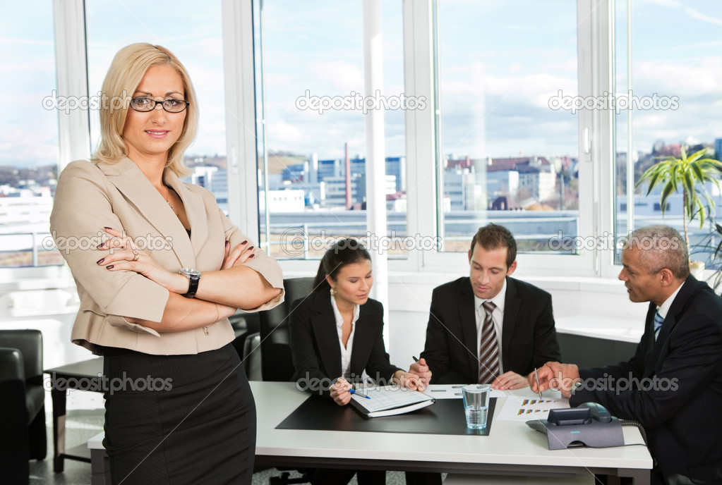 Businesswoman sitting in front. Three business colleagues working in background.  Stock Photo #4737855