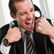 Stressed businessman screaming on the phone — Stock Photo