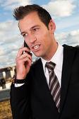 Biznesmen rozmowy na telefon komórkowy poza — Zdjęcie stockowe