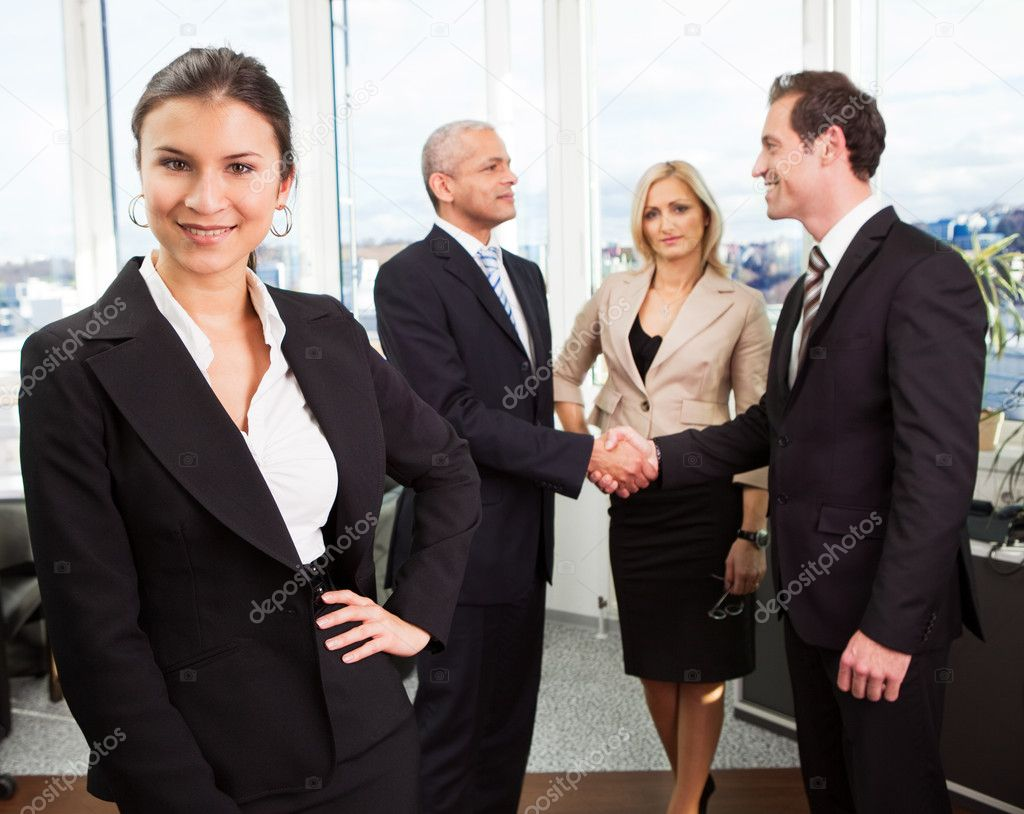 Businesswoman sitting in front. Three business colleagues making agreement in background. — Stock Photo #4874110