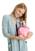 Beautiful young woman saving money — Stock Photo