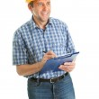 Worker wearing hard hat and taking notes — Stock Photo