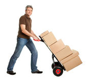 Delivery man pushing hand truck and stack of boxes — Stock Photo