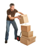 Delivery man staking packages on hand truck — Stock Photo