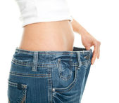 Slim woman pulling oversized jeans — Stock Photo