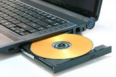 Laptop and DVD isolated on white — Stock Photo
