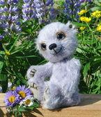 Teddy-bear Chupa among flowers — Stock Photo