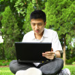 Asian man using computer outdoor — Stock Photo