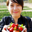 Smile girl give you bowl of strawberries - Stock Photo