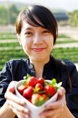 Smile girl give you bowl of strawberries — Stock Photo