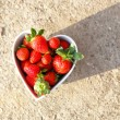 Strawberries in heart shape bowl — Stock Photo