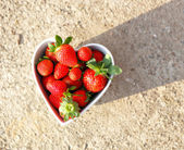 Strawberries in heart shape bowl — Stock fotografie