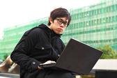 Asian man using computer outdoor — Stock Photo
