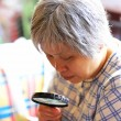Senior woman using magnifier — Stock Photo