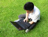Aziatische man met behulp van computer buiten — Stockfoto