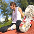 Stock Photo: Woman doing stretching exercise in sport field