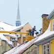 Workers clean snow from a house roof - Stock Photo