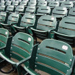 Rows of empty wet green stadium seats, seats number 13, 12, 11 — Stock Photo