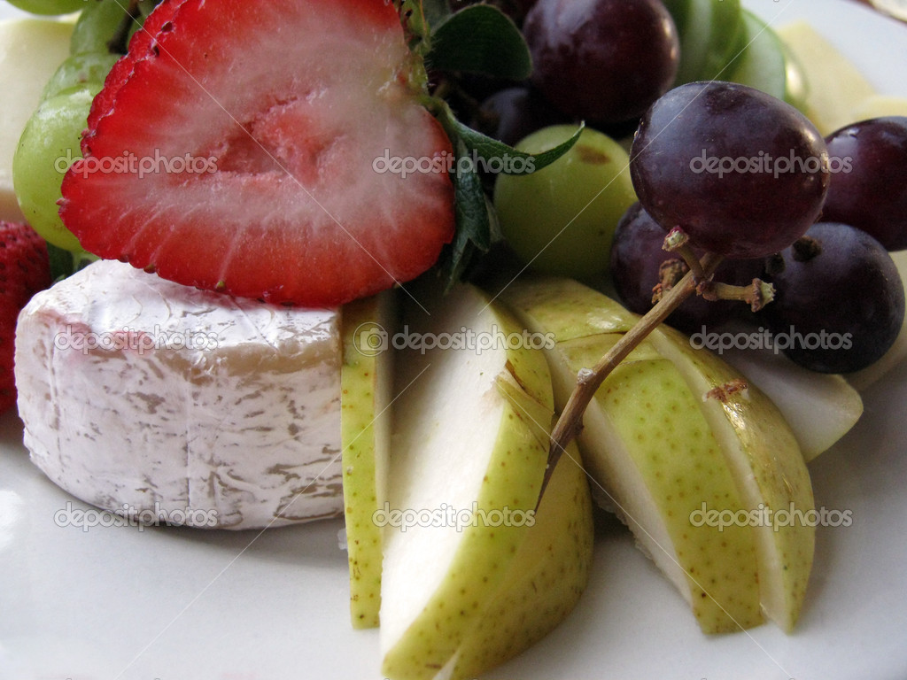 Close-up of Fruit and Cheese on a white plate.  Featuring Strawberries, grapes, pears slices  Stock Photo #5315721