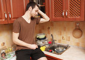 Guy in the kitchen doing the dishes — Stock Photo