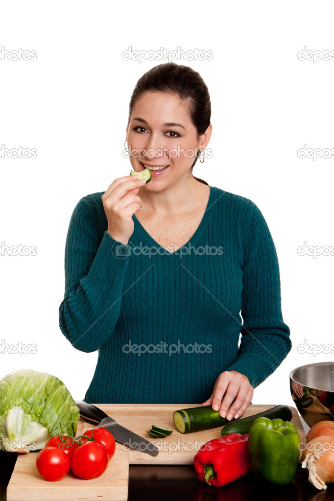 Beautiful woman eating cut cucumber in kitchen, cooking and preparing to make a salad, isolated.  Stock Photo #4093715