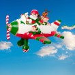 Flying Santa Claus with Elves in Airplane — Stock Photo