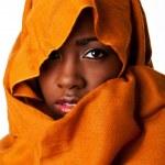 Mysterious female face in ocher head wrap — Stock Photo