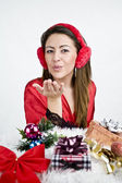 Woman blowing from hand with presents — Stock Photo