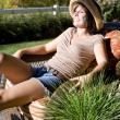 Woman sitting on a patio chair — Stock Photo #4202538