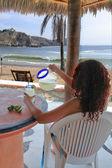 Young woman enjoying a margarita by the beach — Stock Photo