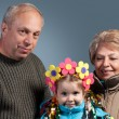 Close-up of a mature couple with their granddaughter - Stock Photo