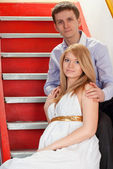 Pregnant couple on a stairway — Stock Photo