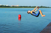 The young sportsman jump in water — Stock Photo