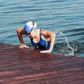 Het meisje sportvrouw springt uit pool op een ponton — Stockfoto
