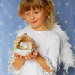 Angel girl holding christmas ball in hand — Stock Photo #4273522