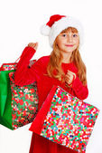 Young girl in santa cloth with gift bags — Stock Photo